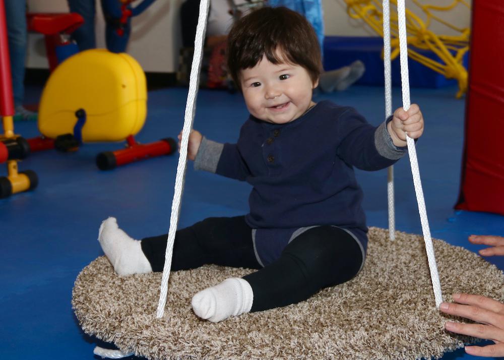 Toddler siting on carpet swing